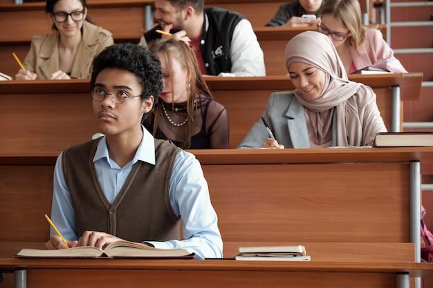 Hedendaagse interculturele universiteitsstudenten die aantekeningen maken terwijl ze aan lange houten bureaus in de collegezaal zitten en naar de professor luisteren tijdens de les