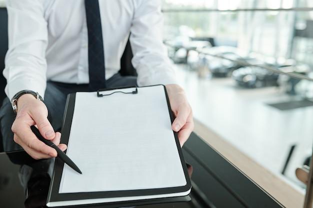 Hedendaagse jonge verkoopmanager of agent in formalwear wijzend naar de linker benedenhoek van het document terwijl hij de klant aanbiedt om een handtekening te zetten