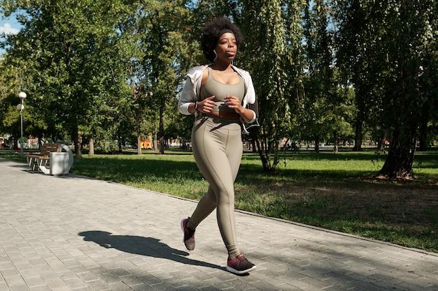 Hedendaagse jonge vrouw in activewear joggen in park