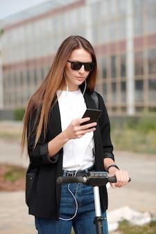Hedendaagse jonge vrouw in oortelefoons en vrijetijdskleding scrollen door afspeellijst in smartphone tijdens het verplaatsen naar het werk op de scooter