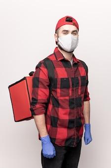 Hedendaagse koerier in werkkleding en beschermend masker en handschoenen met grote rode tas met orders van klanten van café op zijn rug