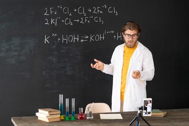 Hedendaagse leraar in whitecoat doet record van scheikunde les voor zijn online publiek op smartphonecamera op bord