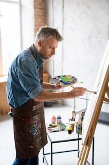 Hedendaagse schilder in werkkleding die palet en penseel vasthoudt terwijl hij voor ezel staat tijdens het overschilderen