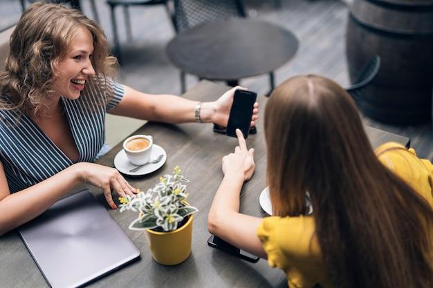Hedendaagse vriendinnen genieten van koffie aan tafel in café terwijl ze smartphone delen en glimlachen