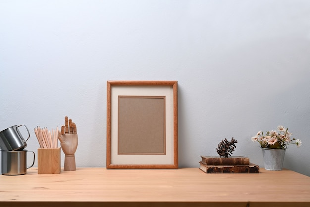 Hedendaagse werkplek met leeg fotolijstje, bloemenpot, potloodhouder en boek op houten tafel.