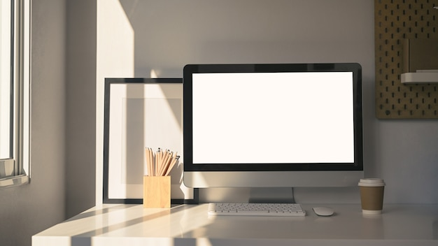 Hedendaagse werkruimte met computer, koffiekopje, potloodhouder en leeg fotolijstje op witte tafel.