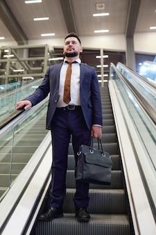 Hedendaagse zakenman van middelbare leeftijd in donkerblauw pak met zwarte leren handtas terwijl hij op de roltrap op de luchthaven staat