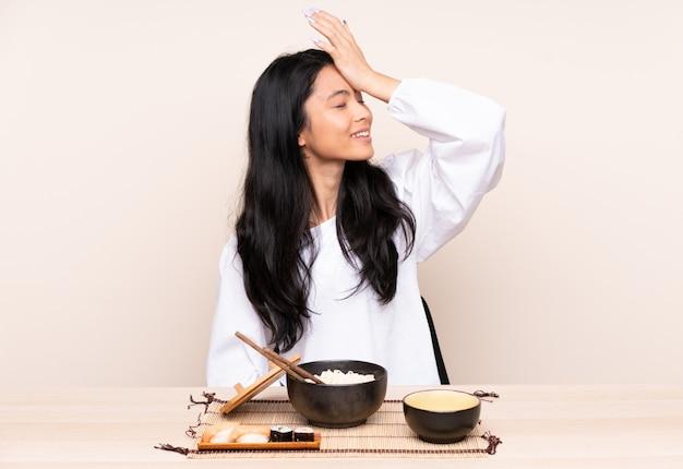 Heeft het tiener aziatische meisje die aziatisch voedsel op beige muur eten iets gerealiseerd en van plan de oplossing