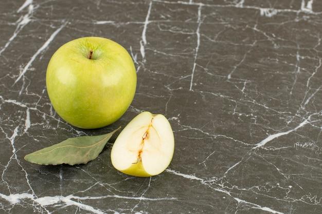 Heel en in plakjes. verse groene appel met blad.