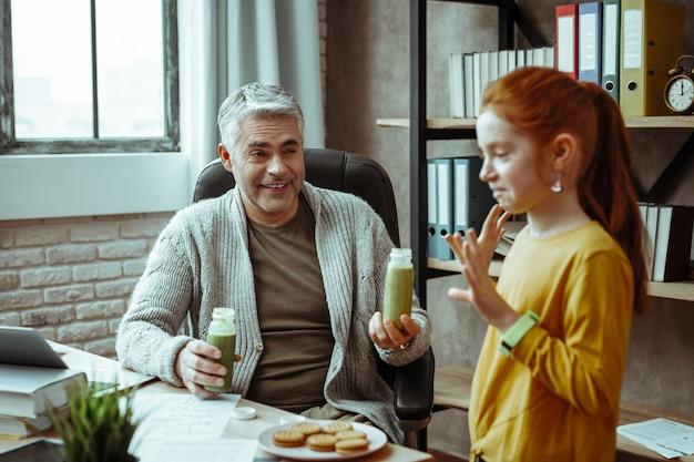 Heel gezond. positieve aardige man die lacht terwijl hij flessen met smoothie vasthoudt