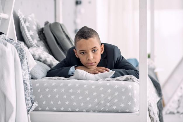 Heel moe. bezorgd afro-amerikaanse jongen liggend op bed tijdens het denken