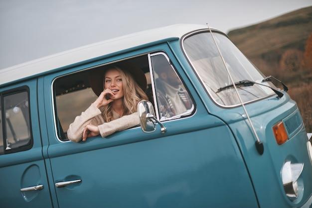 Heel mooi! aantrekkelijke jonge lachende vrouw kijkt uit het raam van de busjes terwijl ze geniet van de autorit met haar vriendje