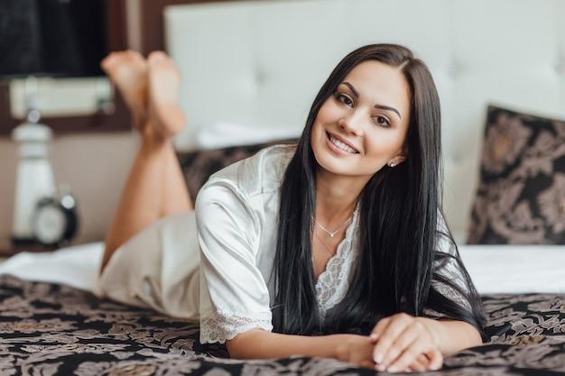 Heel mooi brunette meisje ligt 's ochtends op haar buik in haar kamer.