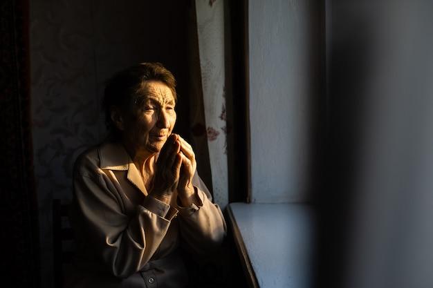 Heel oude vrouw bidt in haar landelijke keuken