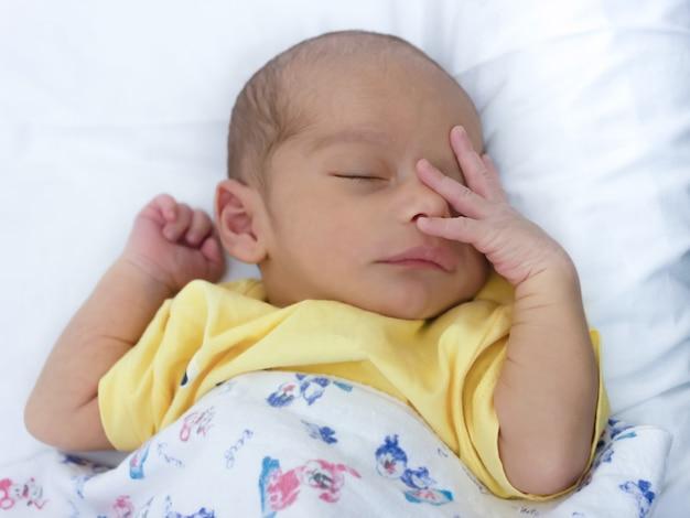 Heel schattig pasgeboren baby slapen op het bed met handen in de buurt van gezicht