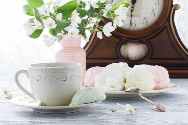 Heemst of zefirdessert op witte plaat met takken van bloeiende appel