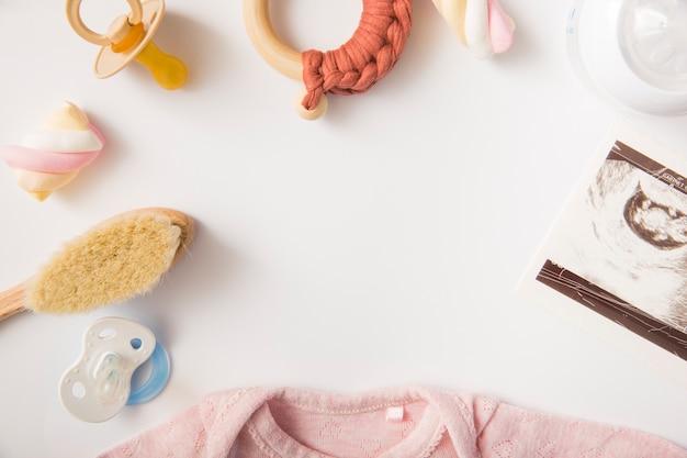 Heemst; roze baby onesie; borstel; fopspeen; melkfles en stuk speelgoed op witte achtergrond