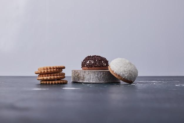 Heemstkoekjes met chocolade en kokospoeder op een stuk hout op blauw.