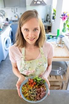Heerful blogger poseert met eten, staat in de keuken, houdt veggy bowl vast, kijkt naar de camera en glimlacht. verticaal schot, hoge hoek. gezond eten of voedselpresentatieconcept