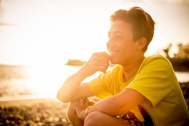 Heerful knappe jonge jongen zittend op het strand glimlachend en kijkend naar de horizon - gelukkige mensen in outdoor vrijetijdsvakantie activiteit tijdens gouden zonsondergang