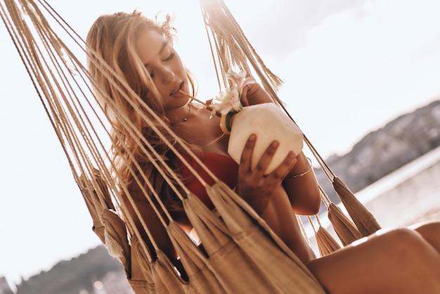 Heerlijk! aantrekkelijke jonge vrouw in rode bikini die geniet van een kokoscocktail terwijl ze in een hangmat op het strand zit