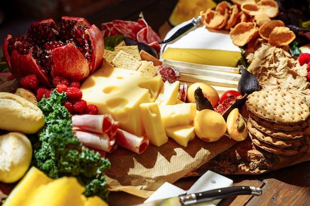 Heerlijk assortiment snacks, kaas, jam, vers fruit en bessen.