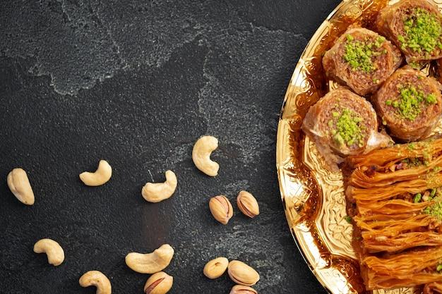 Heerlijk baklava-dessert in oosterse omgeving op zwarte achtergrond