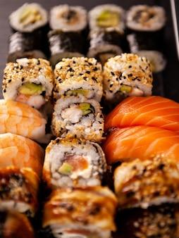 Heerlijk bord met verschillende verse sushi op donkere steen?