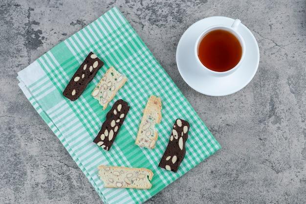 Heerlijk brood beschuit met noten en kopje aroma thee op marmeren oppervlak.