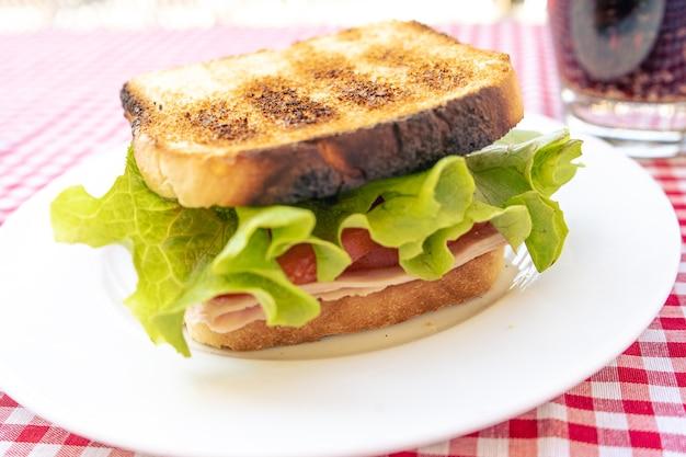 Heerlijk broodje ham, tomaat en sla.