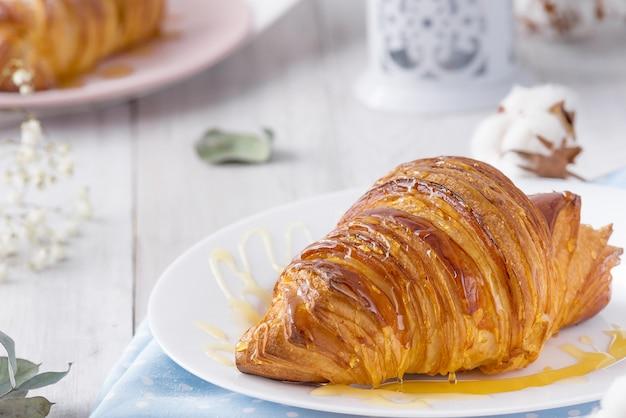 Heerlijk continentaal ontbijt met verse, schilferige franse croissants met honing, close-up op de croissants. met witte katoenen bloemen. provençaalse rustieke stijl.