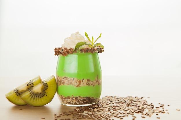 Heerlijk dessert met kiwi en havermoutzaadjes gedecoreerd met room en munt