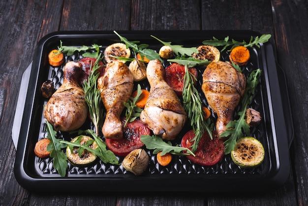 Heerlijk diner voor het hele gezin, gebakken kippenpoten in een pan, gegrilde groenten, aromatische kruiden