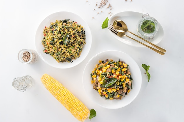 Heerlijk en gezond indonesisch eten in witte borden met gouden vork en lepel op witte achtergrond