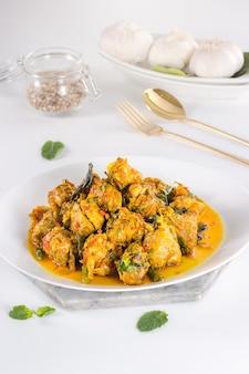 Heerlijk en gezond indonesisch eten in witte plaat met gouden vork en lepel op witte achtergrond