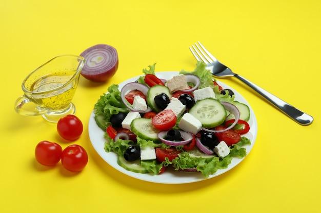 Heerlijk eten met griekse salade op geel oppervlak