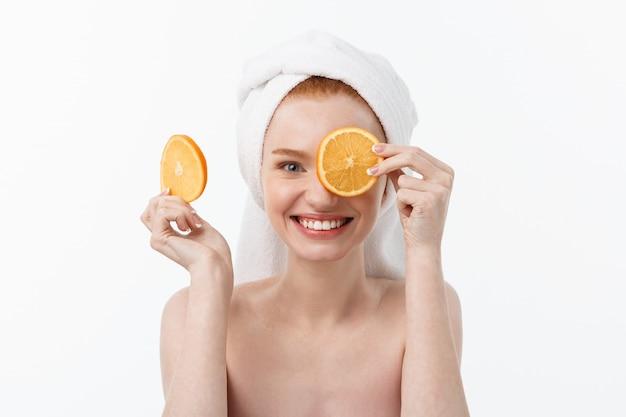 Heerlijk eten voor een gezonde levensstijl. het mooie jonge shirtless stuk dat van de vrouwenholding van sinaasappel zich bevindt tegen.