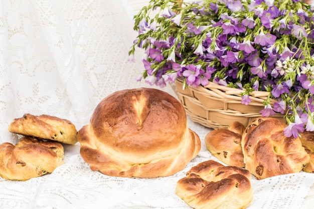 Heerlijk gebak (brood en broodjes met rozijnen) en boeket linnen in rieten mand. retro-stijl, vintage
