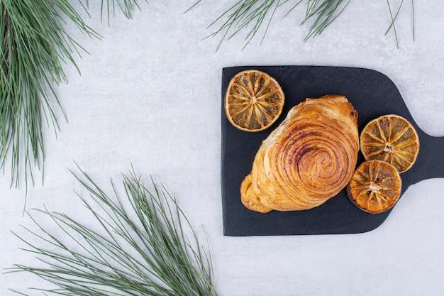 Heerlijk gebak met gedroogde stukjes sinaasappel op een zwart bord. hoge kwaliteit foto