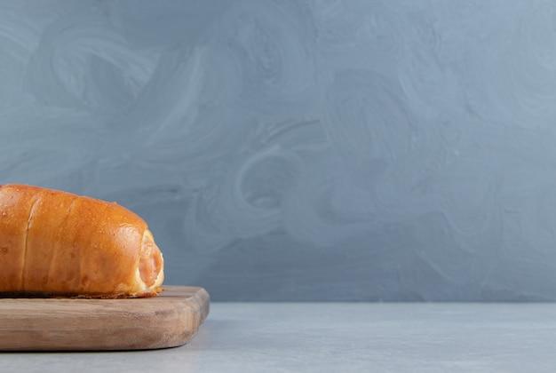 Heerlijk gebak met worstjes op een houten bord.