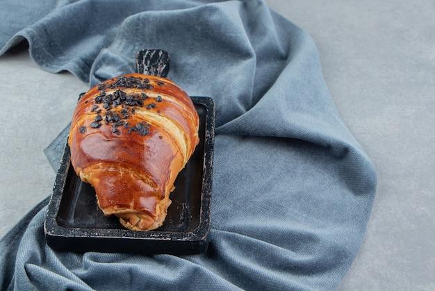 Heerlijk gebak op zwart bord met doek.