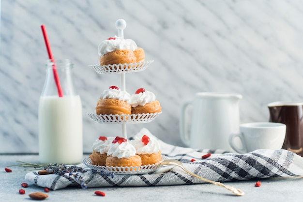 Heerlijk gebak schikt op een taartstandaard in de buurt van een melkfles en notenvoedsel op een betonnen oppervlak