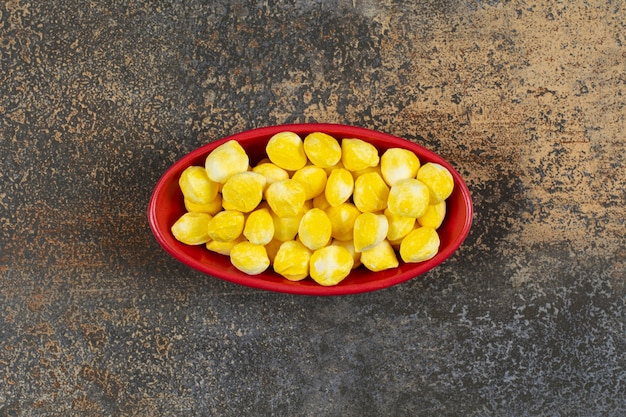 Heerlijk geel suikergoed in rode kom.