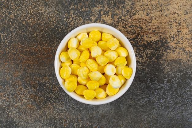 Heerlijk geel suikergoed in witte kom.