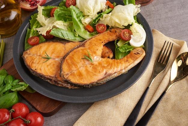 Heerlijk gekookte zalmvisfilets. gegrilde zalm visfilet en verse groene sla plantaardige tomatensalade. evenwichtig voedingsconcept voor schoon eten flexitarisch mediterraan dieet.