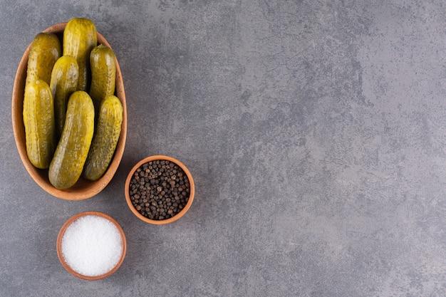 Heerlijk gemarineerde ingelegde komkommers met zout en peperkorrels.