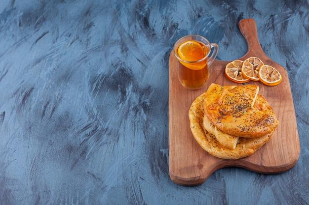 Heerlijk gesneden gebak met zaden en een glas thee op een houten bord.
