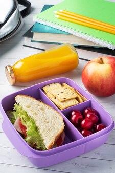 Heerlijk gezond broodje in een lunchbox, koekjes en kersen. neem de lunch mee naar school of kantoor. sap in een fles en een appel.