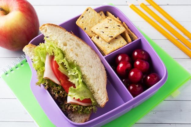 Heerlijk gezond broodje in een lunchbox, koekjes en kersen. neem de lunch mee naar school of kantoor.