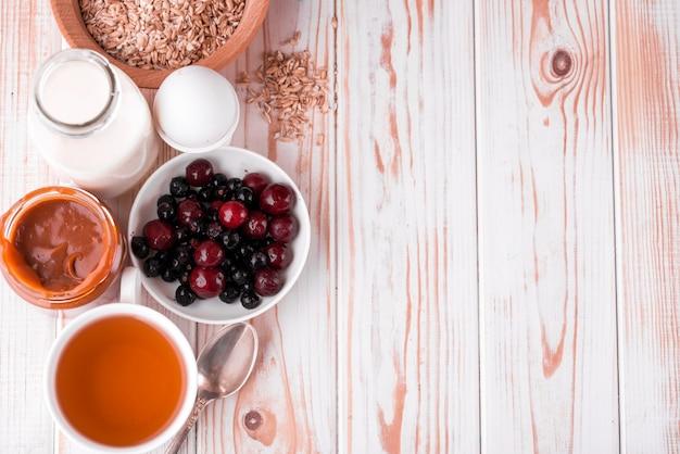 Heerlijk, gezond, stevig ontbijt op de witte tafel. eieren, havermout, melk, thee, bananentoost, huisgemaakte gezouten karamel, pannenkoeken met fruit, sinaasappelsap.
